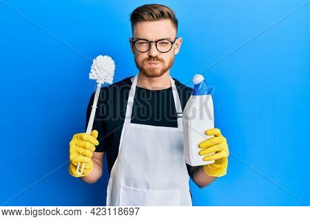 Young redhead man doing bathroom housework with toilet brush puffing cheeks with funny face. mouth inflated with air, catching air.