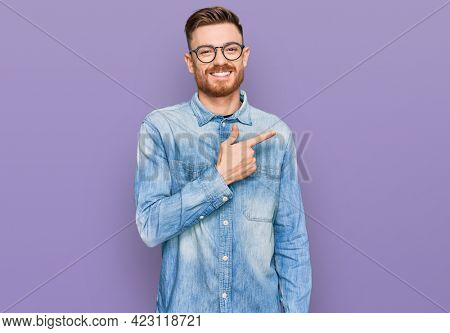 Young redhead man wearing casual denim shirt cheerful with a smile of face pointing with hand and finger up to the side with happy and natural expression on face