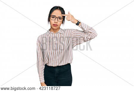 Young hispanic girl wearing casual clothes and glasses pointing unhappy to pimple on forehead, ugly infection of blackhead. acne and skin problem
