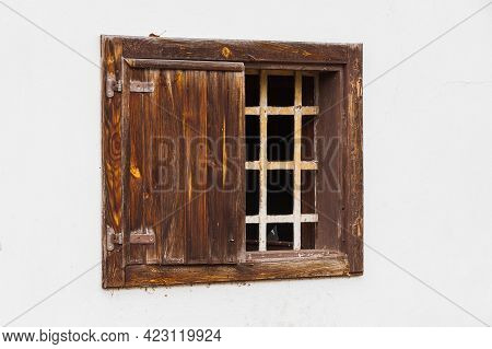 Window With A Wooden Frame On A White Wall Of The House. There Is A Grille In The Windows. There Are