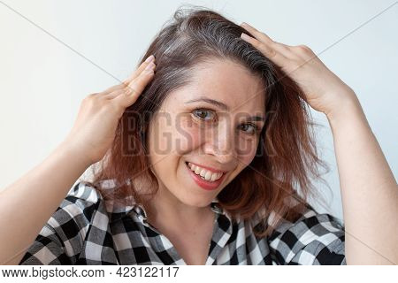 Young Woman Shows Her Gray Hair Roots. Early Aging Concept.