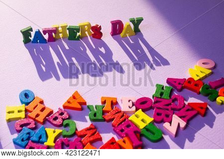Child's Toy Letters Spelling Fathers Day With A Large Shadow Next To Randomly Lying Letters On Purpl
