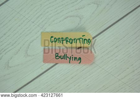 Confronting Bullying Write On Sticky Notes Isolated On Wooden Table.