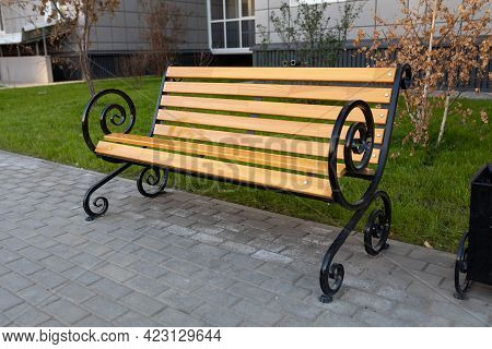 Classic Wooden Bench With Metal Armrests Near An Apartment Building. Paving Slabs Under The Bench. I