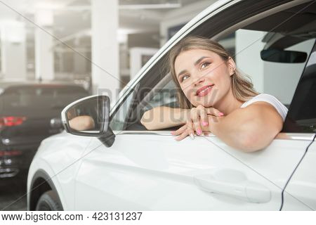 Charming Young Woman Looking Away Dreamily, Ditting In A New Automobile At Dealership