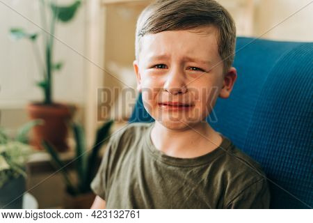 Close Up Portrait Of Crying Little Kid Boy, Sitting On Couch Indoors At Home. Upset Child
