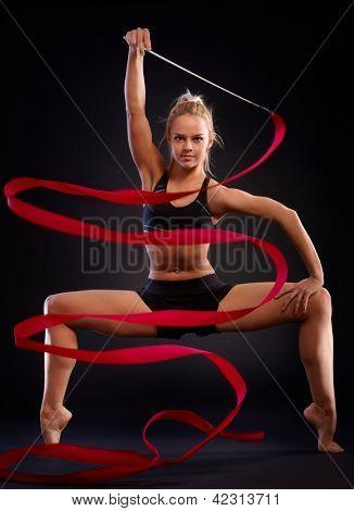 Ritmische gymnast in een mooie houding gebruikend lint op zwarte achtergrond.