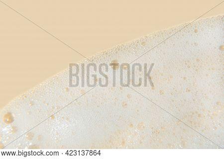 White Cosmetics Foam Texture On Beige Background. Cleanser, Shampoo Bubbles, Wash - Liquid Soap, Sho