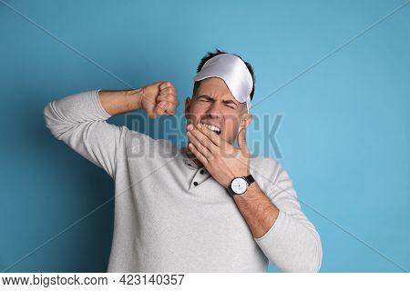 Tired Man With Sleeping Mask Yawning On Light Blue Background