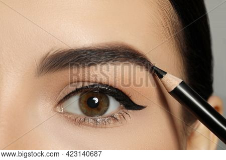 Young Woman Correcting Eyebrow Shape With Pencil, Closeup View