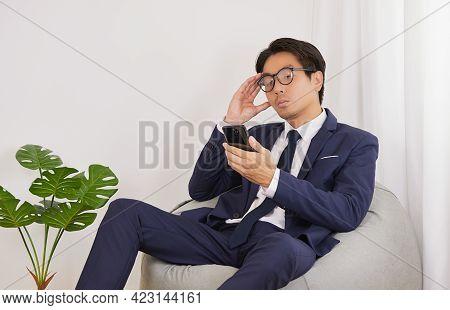 Asian Financial Advisor Wear Glasses Headache From Thinking On Bean Bag In Home Office. Businessman