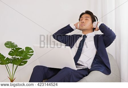 Asian Financial Advisor Wear Headphone Using Laptop For Listen To Music. Businessman In Relax Time F