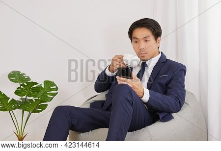 Asian Financial Advisor Drink Coffee See Smartphone On Bean Bag In Home Office. Businessman Work At
