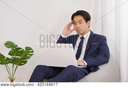 Asian Financial Advisor Headache And Using Laptop Computer On Bean Bag In Home Office. Businessman W