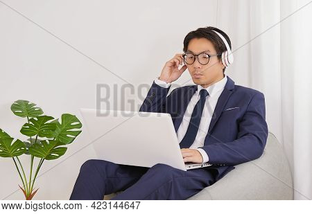 Asian Financial Advisor Wear Glasses Touch Headphone And Use Laptop In Home Office. Businessman Work
