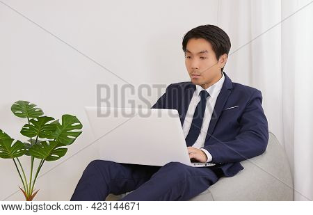 Asian Financial Advisor Using Laptop Computer On Bean Bag In Home Office. Businessman Work At Home F