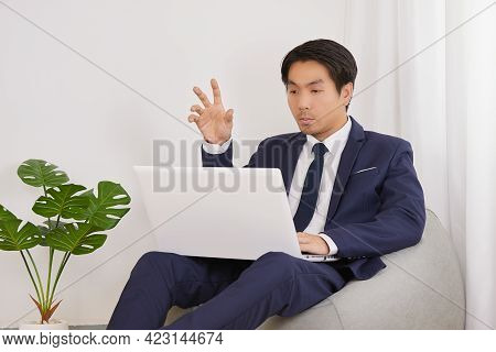 Asian Financial Advisor Video Conference With Customer By Laptop Computer In Home Office. Businessma