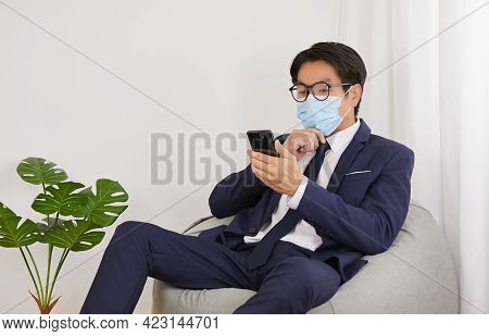 Asian Financial Advisor Wear Face Mask And Glasses Serious Thinking In Home Cafe Office.businessman
