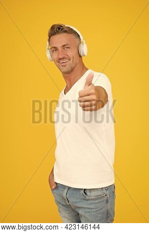 Because Your Ears Deserve The Best. Handsome Man Give Thumbs Up Yellow Background. Headphones Techno