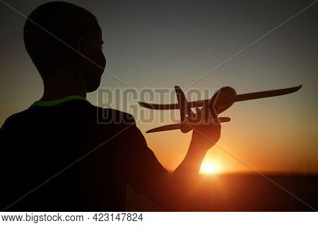 Boy Throws A Toy Airplane In The Summer At Sunset. A Child Plays With A Toy Airplane, Dreams Of A Tr