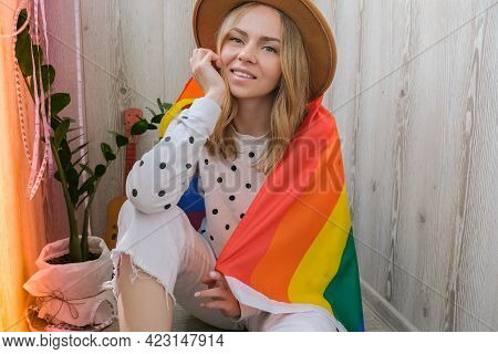 Young Blonde Millennial Hippie Woman With Rainbow Lgbtq Flag At Home Balcony. Peace And Freedom The