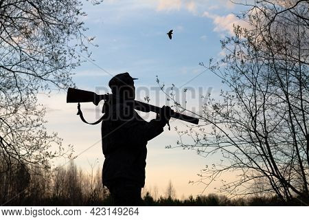 The Dark Silhouette Of A Hunter With A Shotgun On His Shoulder Against The Evening Sky. He Stands In