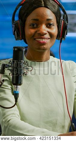 Portrait Of African Smiling Blogger Looking At Camera Before Starting Live Video From Home Studio Po