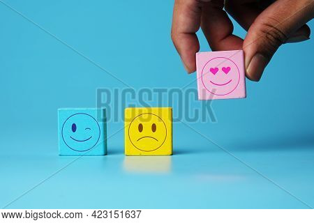 A Picture Of Hand Taking Love Emoticon With Winking And Sad Emoticon At Wooden Block On Blue Backgro
