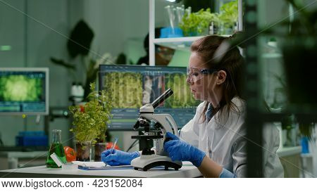 Pharmaceutical Scientist Looking At Green Leaf Sample On Microscope While Writing Genetic Test On No