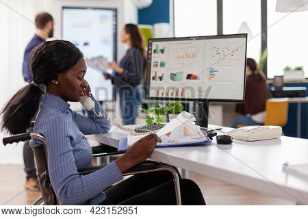 Busy Paralysed Handicapped Black Employee Answering Phone Talking With Colleague Sitting Immobilized