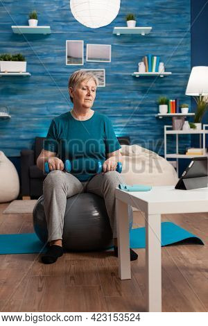 Senior Woman Exercising Body Muscles Doing Arms Exercise Sitting On Swiss Ball In Living Room. Pensi