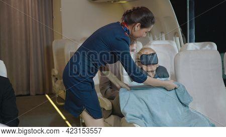 Happy Stewardess Taking Care Of Passenger Adult Businesswoman, Air Hostess Or Flight Attendant Woman
