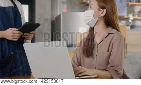 Asian Young Beautiful Businesswoman Smile Using Laptop Computer Online At Coffee Shop, Hospitable Wa