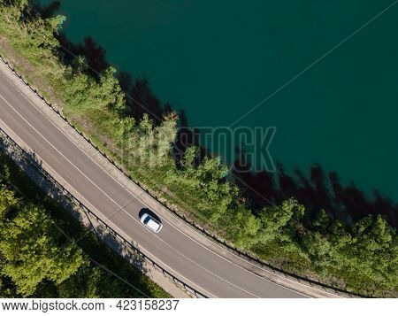 Aerial view of road between green summer forest and lake