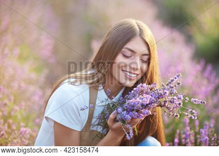 Young Smiling With Teeth Woman Wearing Farm Outfit Smelling Lavender Bouquet In Summer, Sunset. Sele