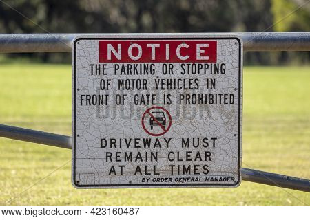Photograph Of A Do Not Park And Keep Driveway Clear Sign Bolted To A Gate At A Sporting Field