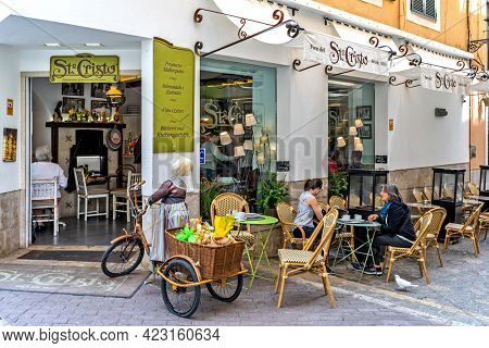 PALMA, SPAIN - APRIL 12, 2019: People sitting outside of Forn del Santo Cristo - famous bakery in historic center of Palma, founded in 1910, offers traditional Mallorcan specialties.