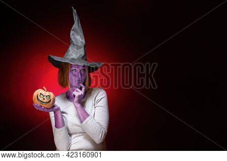 Halloween. A Young Woman With Purple Skin In A Black Witch Hat Is Holding A Pumpkin With A Zombie Fa