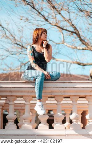 A Young Smiling Woman With Tattoed Hand Sits On The Balustrade And Looking At The Right Side. Vertic