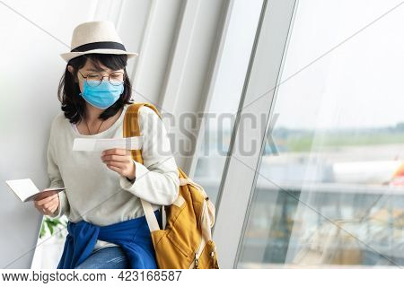 Asian Female Tourist Wearing Protective Face Mask Holding Boarding Pass Waiting For The Flight Near