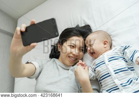 Asian Young Mother Comforting Or Consoling Her Little Toddler Son While Holding Mobile Phone. Sadnes