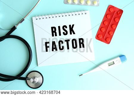 The Text Risk Factor Is Written On A White Notepad That Lies Next To The Stethoscope And Pills On A