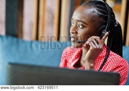 African American Woman Works In A Call Center Operator And Customer Service Agent Wearing Microphone