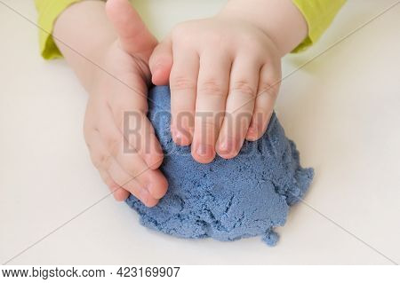 Childrens Hands Close-up, Sculpt, Play With Blue Kinetic Sand. The Concept Is Based On The Developme