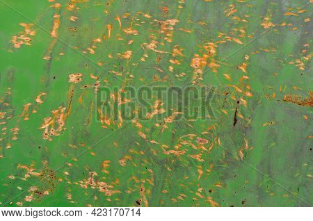 Chaotic Yellow Dots And Spots Of Rust On The Green Painted Metal Wall. Rusty Metal And Paint.  Corro