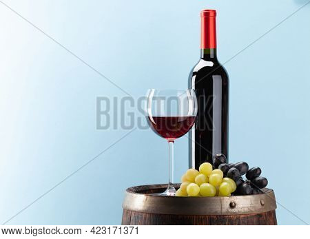 Wine bottle with red wine, wineglass and grapes on old wooden barrel in front of blue background with copy space