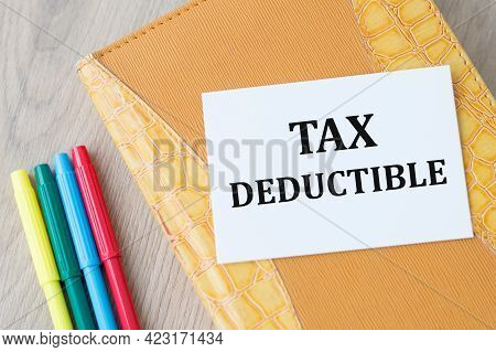 Yellow Notepad With A White Card On Which The Text Tax Deductible On A Wooden Table Next To Colored