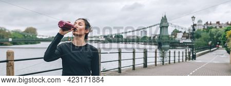 Beautiful Young Slim Woman Is Drinking Water While Jogging Along The Embankment Of The River In Lond