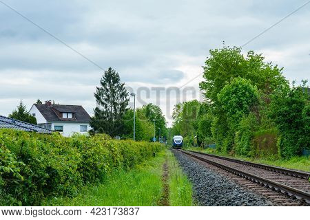 A Regional Train Is Approaching On Rails On A Cloudy Day. Gray Clouds In The Sky.
