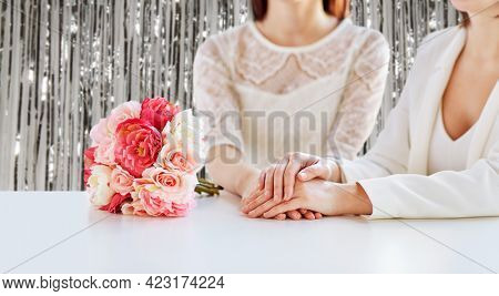 homosexuality, same-sex marriage and lgbt concept - close up of happy married lesbian couple with flower bunch on wedding over foil party curtain on background